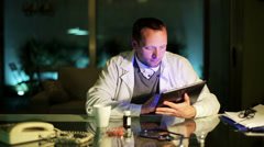 Doctor working on tablet at night in office by the desk. - stock footage
