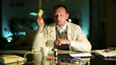Stock Video Footage of Doctor picking up phone at night in office.
