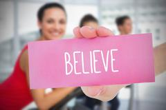 Woman holding pink card saying believe Stock Illustration