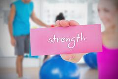 Stock Illustration of Fit blonde holding card saying strength