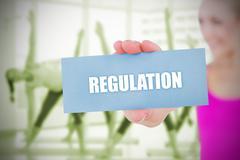 Stock Illustration of Fit blonde holding card saying regulation