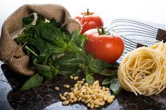 italian cooking ingredients on a black granite tabletop. - stock photo