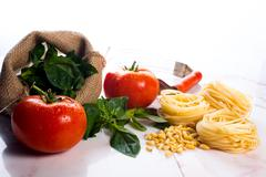 Italian cooking ingredients on a white marble tabletop. Stock Photos