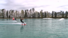 WAKEBOARDER WAKEBOARDING RIDERS FLIP JUMP AT CABLE PARK HD Stock Footage