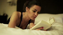 Woman reading book and lying on bed, steadycam shot. Stock Footage