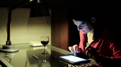 Woman watching tablet at night by the table. Stock Footage