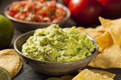green homemade guacamole with tortilla chips - stock photo