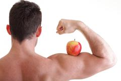 athletic sexy male body builder holding red apple - stock photo