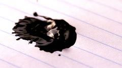 Black ink falling on lined paper Stock Footage