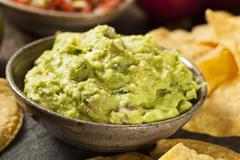 Stock Photo of green homemade guacamole with tortilla chips