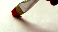 Painter painting with red paint and paintbrush - stock footage
