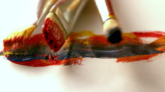 Paintbrushes dropping on page with brushstrokes - stock footage