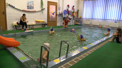 Small children play and swim in the pool in a manger.  Paddling pool. Stock Footage