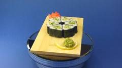 Sushi rolls with avocado on wooden plate with wasabi. - stock footage