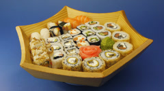 Big sushi set on a wooden plate on blue background Stock Footage