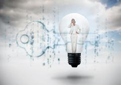 Composite image of thinking businesswoman in light bulb - stock illustration