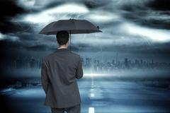 Stock Illustration of Composite image of rear view of classy businessman holding grey umbrella