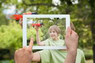 Stock Illustration of Composite image of hand holding tablet pc