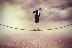 Stock Illustration of Composite image of businesswoman performing a balancing act