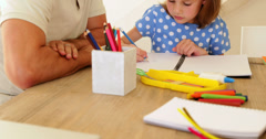 Father and daughter drawing together at the table Stock Footage