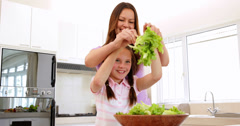 Mother showing her daughter how to toss a salad Stock Footage