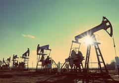 Stock Photo of oil pumps silhouette against sun - vintage retro style