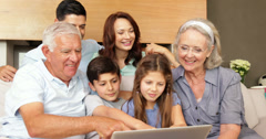 Extended family using the laptop together on the couch Stock Footage