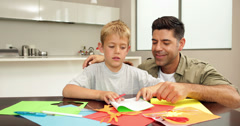 Father and son doing arts and crafts at kitchen table Stock Footage