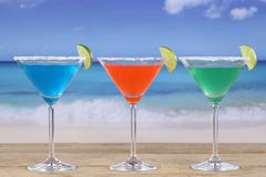 colorful cocktails in martini glasses on the beach - stock photo