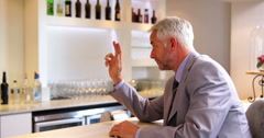 Businessman ordering a drink from barmaid Stock Footage