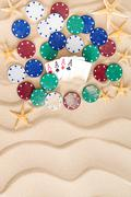 four aces with poker chips on beach sand - stock photo
