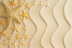 starfish on golden beach sand with wavy lines - stock photo
