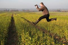 Freestyle photographer in rapeseed field - stock photo