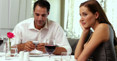 Bored woman waiting for her date to stop texting Stock Footage
