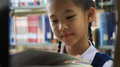 Little Asian student reading book in library Stock Footage