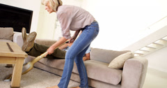 Woman hoovering the carpet while partner relaxes watching tv Stock Footage