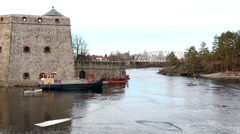 Ice rafts and rowing boat moving by a medieval castle in springtime Stock Footage