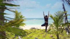 Hispanic does yoga on beach Stock Footage