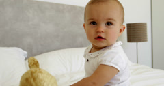 Cute baby girl playing with teddy bear on bed - stock footage