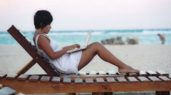 Woman using laptop on beach Stock Footage