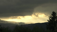 Sun rays penetrate through clouds and illuminated the hills Stock Footage
