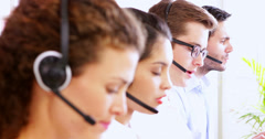Row of call centre agents talking at their desk Stock Footage