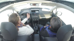 Instructor and the woman behind the wheel. The camera on the ceiling of the car Stock Footage