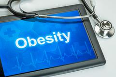 tablet with the diagnosis obesity on the display - stock photo