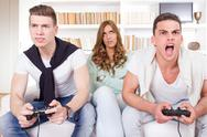 Stock Photo of bored women between two casual passionate men playing video game