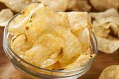 Unhealthy crispy potato chips Stock Photos