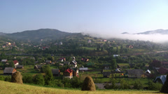 Train passing a village in Carpathians Stock Footage