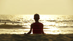Practicing yoga at sunset on Goa beach Stock Footage