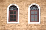 Stock Photo of windows of homes with brick wall surround.