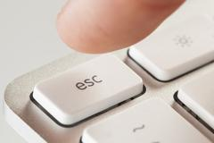 finger pressing escape on a grey computer keyboard - stock photo